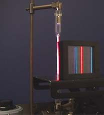 The pink coloured Hydrogen gas discharge tube is analysed using a diffraction grating. The actual coloured light in the spectrum can be clearly identified as red, blue and violet.